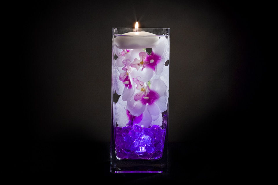 Violet floral centerpiece with led lights and floating candle